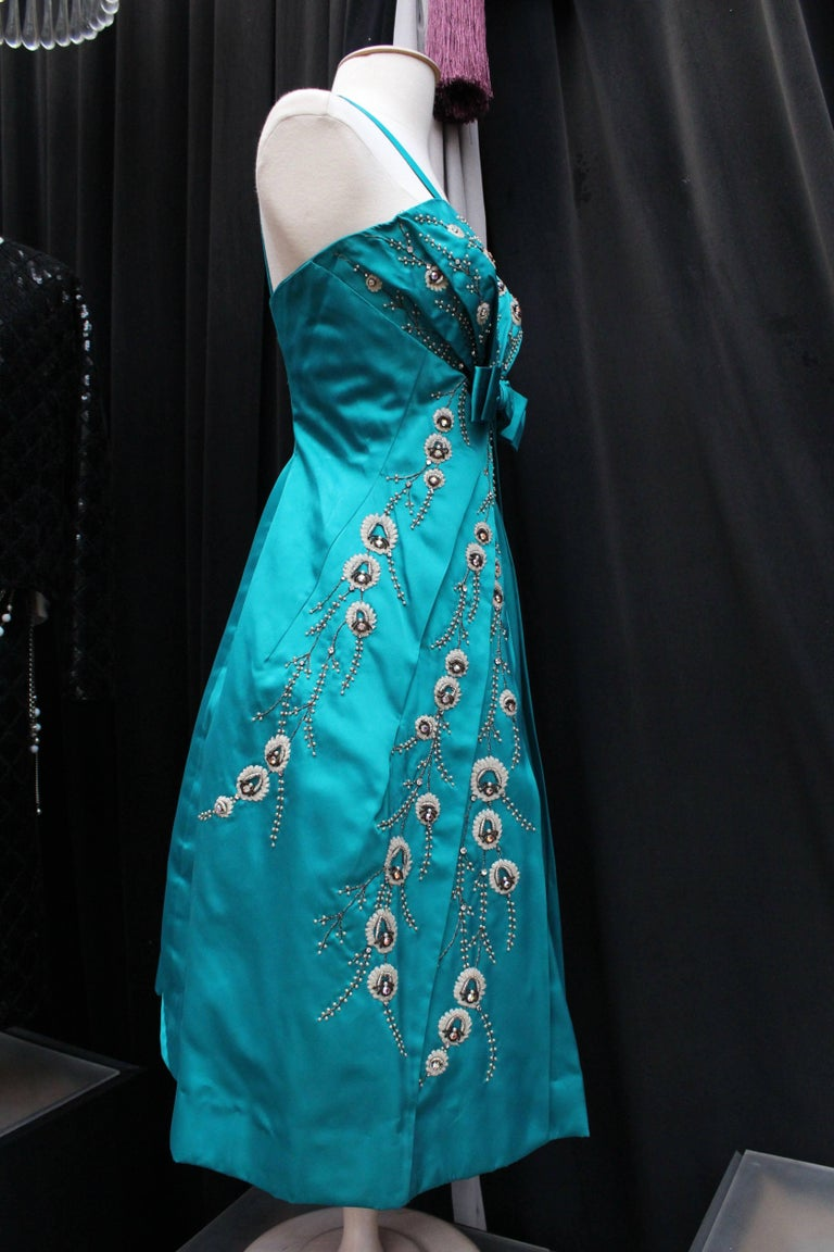 MODISSA – Lovely turquoise satin puffball shaped cocktail dress. It is embellished with a wide bow at bust and pearly beads and rhinestones embroideries representing branches. The delicate pleat work runs upwards from the bow towards the shoulders,