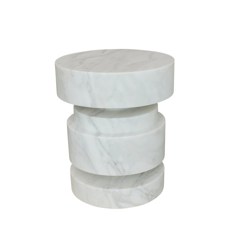 Sculptural side table carved from a solid block of calacatta gold marble. Multiple pieces can be grouped together as a cocktail table. Available in custom sizes and shapes. We partner with clients to develop customized sculptural forms that can be