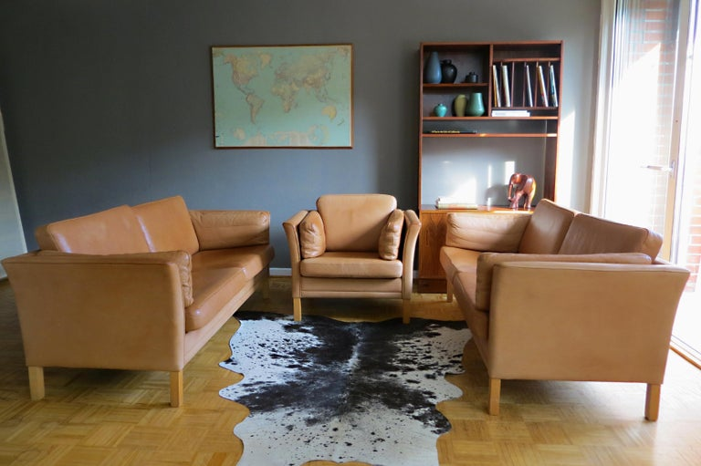A very comfortable living room leather sofa set by Mogens Hansen Denmark from the late 1960s-early 1970s is being offered here. This offer includes 2x three-seat leather sofas and one easy chair. The living room suite is reminiscent of the designs