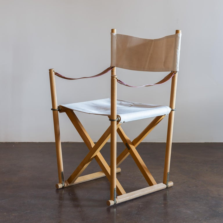 Set of six beech and canvas folding chairs with storage stand, by Mogens Koch for Rud Rasmussen, Denmark. Natural linen canvas sling seats and backs with full-grain leather straps and brass fittings.