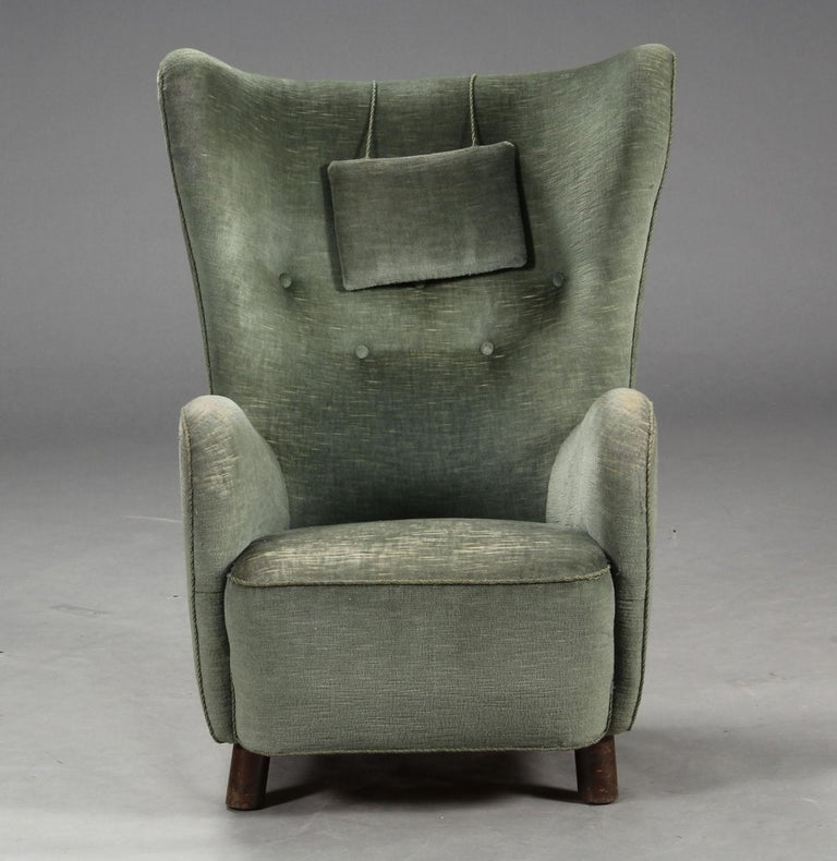 Danish furniture manufacturer, Mogens Lassen style. High-backed armchair upholstered in green velour, curved armrests and wingbacks, round forelegs of stained beech wood, 1930s. Heavy wear on armrests and seat.