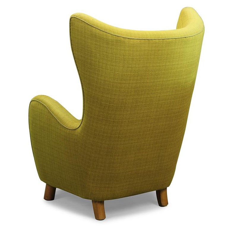 Mogens Lasse style - High-Backed lounge chair  The high-backed wing chair, manufactured by Danish Furniture Producer has minimalistic curved armrests and the typical round, wooden beech legs.  The seat cover is upholstered with a beautiful green