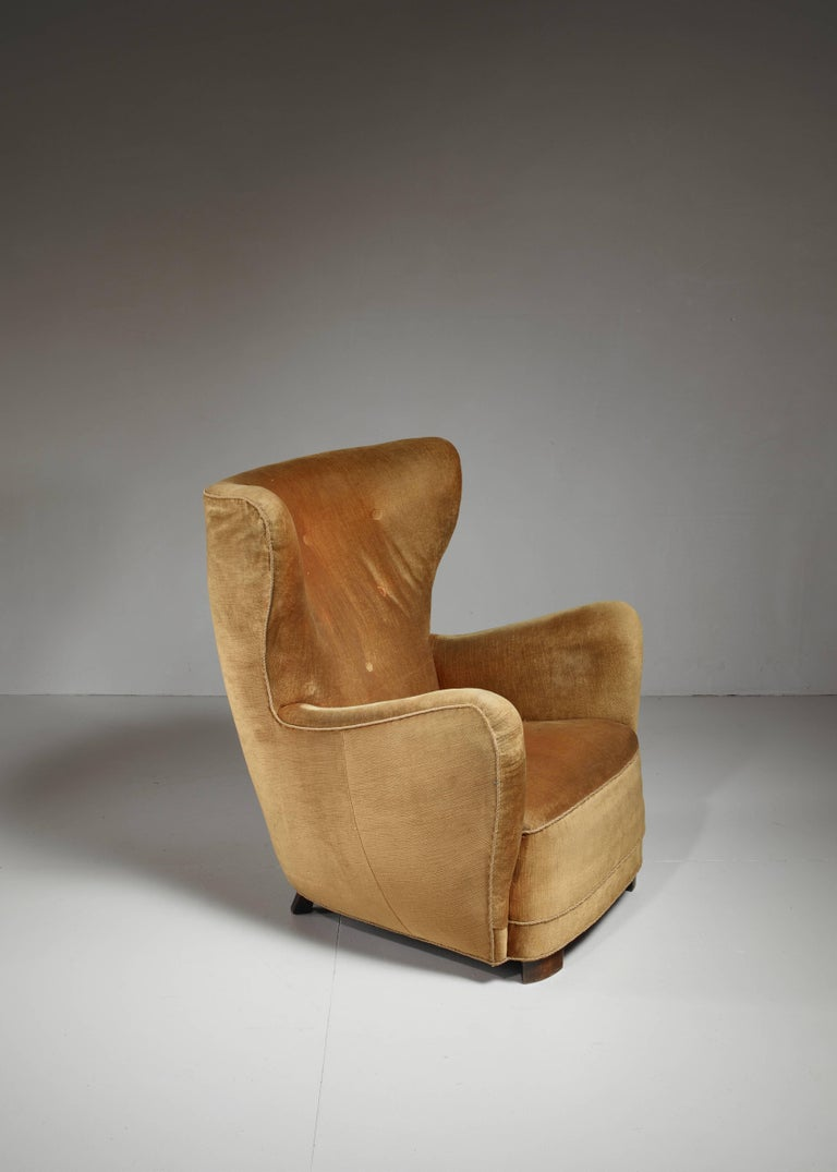 A Danish high, wingback easy chair in the style of Mogens Lassen with legs of stained beech. The chair is upholstered with ochre yellow velour's and needs re-upholstery. The backrest is button fitted.