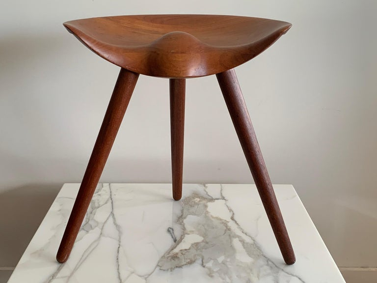 A classic vintage and original Mogens Lassen three legged stool in teak. Beautiful patina, great sculptural form.