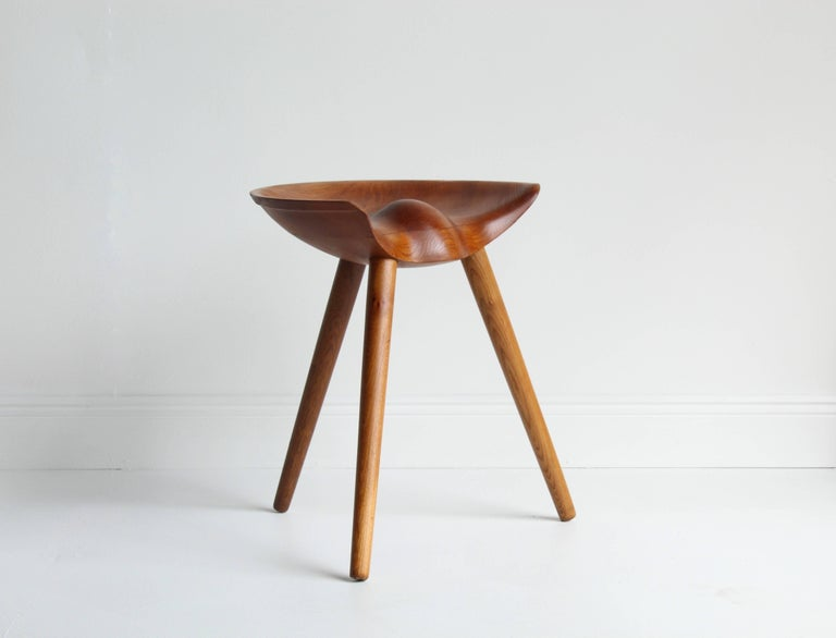 A modernist stool designed by architect Mogens Lassen, made by cabinetmaker K. Thomsen. The seat is sculpted from elm with oak turned legs. This model was presented at The Copenhagen Cabinetmakers' Guild Exhibition at Designmuseum, Denmark, 1942.