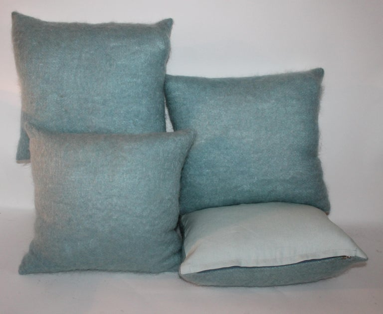 These fine robin egg blue mohair pillows have light blue cotton linen backings. The inserts are down and feather fill. Sold as collection of four.