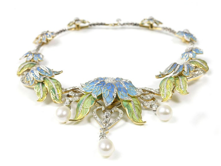 A Moira Collection, plique-à-jour enamel flower necklace, with sky blue plique-à-jour enamel flowers, and green plique-à-jour leaves, with old-cut and eight-cut diamonds and three large cultured drop pearls at the front, mounted in silver-upon-gold.