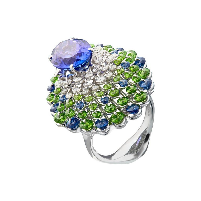 A vivid and clean 5ct Tanzanite is mounted in the innovative setting inspired by graceful peacock. Waltzing Brilliance technology is an innovative jewellery invention patented by Viktor Moiseikin, which a diamond facet gem is secured by two points: