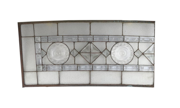 This stunningly crafted window features geometric molded glass on handsome textured glass. A symmetrical mix of sharp lines and curved shapes give each of the 4 pieces of this massive window a unique look.