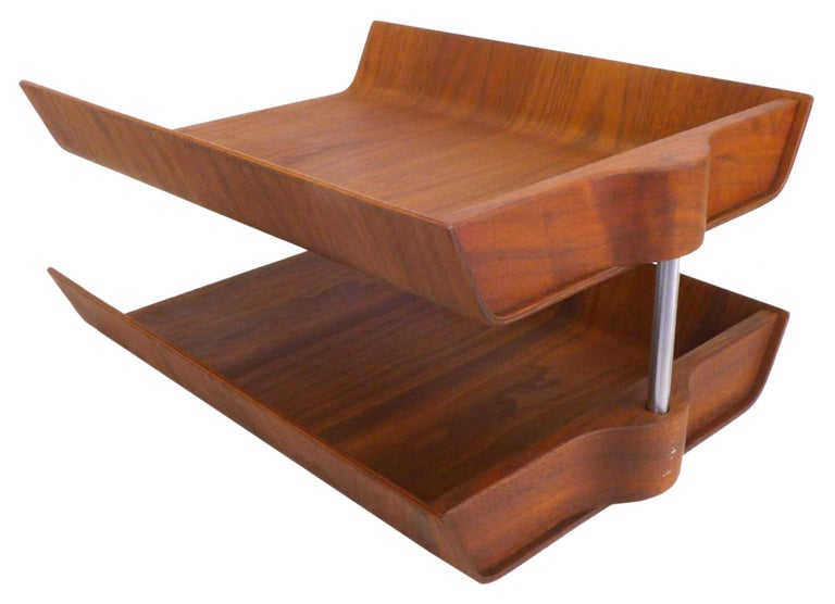 An architectural, two-tier, molded walnut plywood letter tray by Florence Knoll. An outstanding desk accessory as beautiful and iconic as it is practical. An American midcentury classic in wonderful original condition retaining Knoll label at the