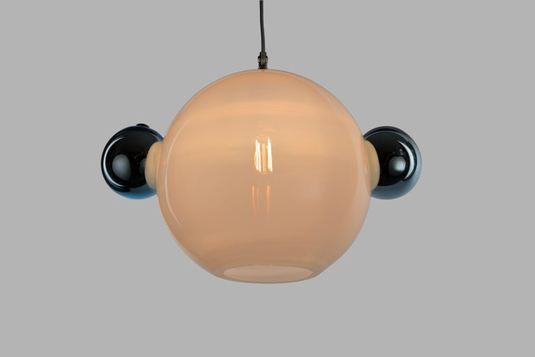 The Molecule Pendant - Double is a calculated arrangement of handblown glass orbs meant to resemble a simple molecular structure. It consists of an opaline 12