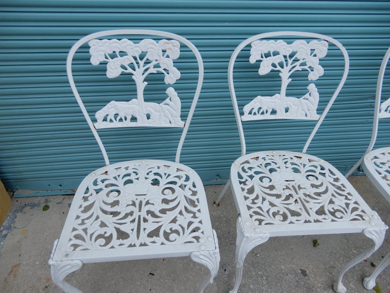 A set of 4 cast aluminum figural dining chairs. Molla who worked on Long Island New York is best known for producing furniture in cast aluminum. The rare design of the chairs show a Shepard with his sheep sitting beneath a large tree. Molla is