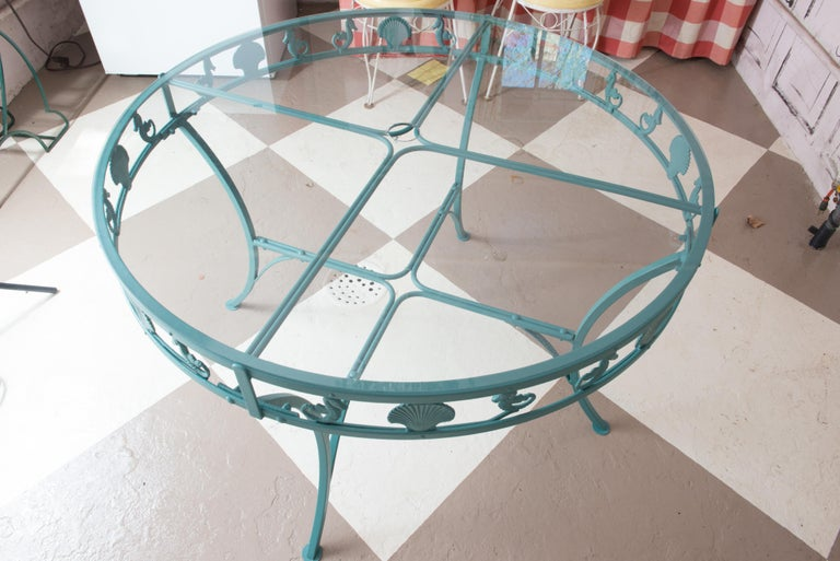 Unusual mid-century Molla round aluminum, glass top garden table with clam shells and seahorses adorning the apron. Painted cast aluminum table with curved legs ending in round feet.