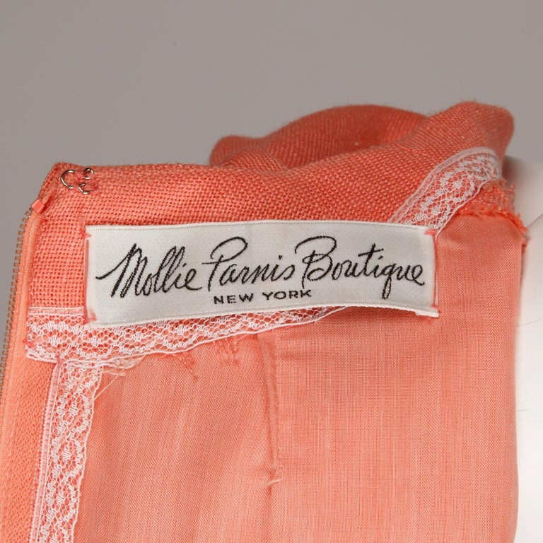 Beautifully done vintage 1960s coral linen dress by Mollie Parnis with short sleeves and a front box pleat. Fully lined with rear zip and hook closure. Fits like a modern size medium. The bust measures 38