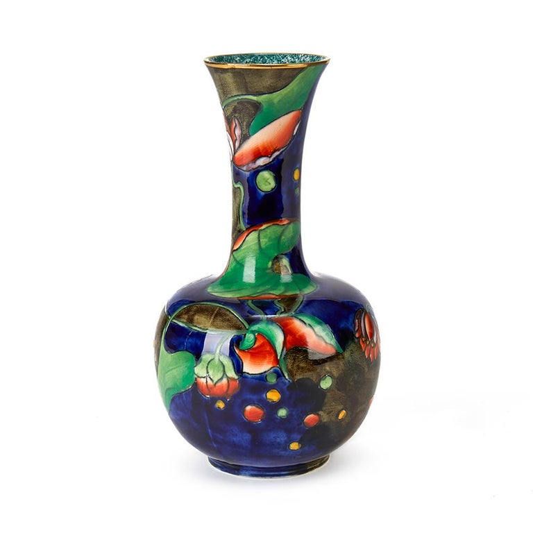 A very fine hand painted S Hancock & Sons Coronaware art pottery bottle shaped vase hand painted and signed by Molly Hancock in the Water Lily pattern in colored enamels on a blue ground. The vase has a gilded top rim with mottled finish to the