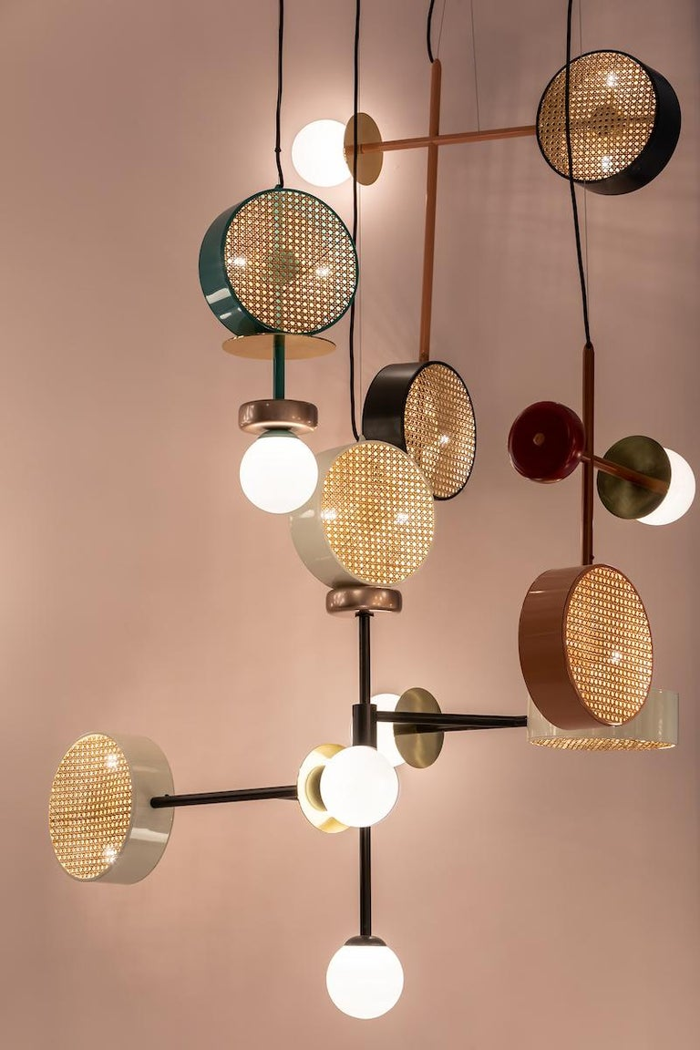 A perfect suspension of round shapes, rattan mesh and brass details intertwined with delicate and opaque glass globes.