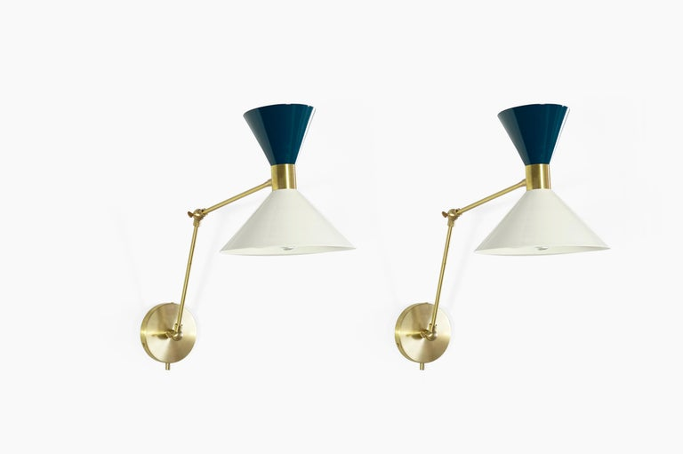 Monarch is a large scale wall-mount reading lamp or sconce with articulated arms. The wide brass band and dramatically scaled flared cone makes the Monarch a strong design statement. Swiveling head allows for cone adjustment. Arms articulate at both
