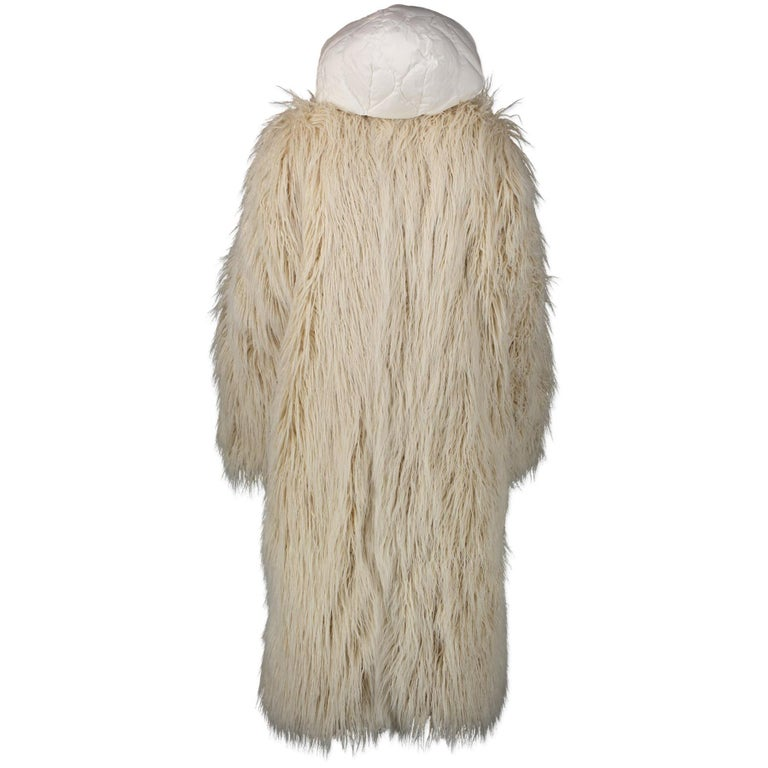 This gorgeous Moncler coat features two styles in one, with a removable white faux-shearling coat over a white quilted jacket underneath. The jacket comes with zipped pockets and a drawcord hood. Style this beautiful coat with a mom jeans and