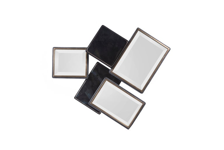 The Mondrian mirror small is a playful graphic piece with it's geometric mixture of mirror parts, blue and black pen shell parts, and black shagreen parts that are placed on different levels. The shagreen/shell parts have a discreet metal