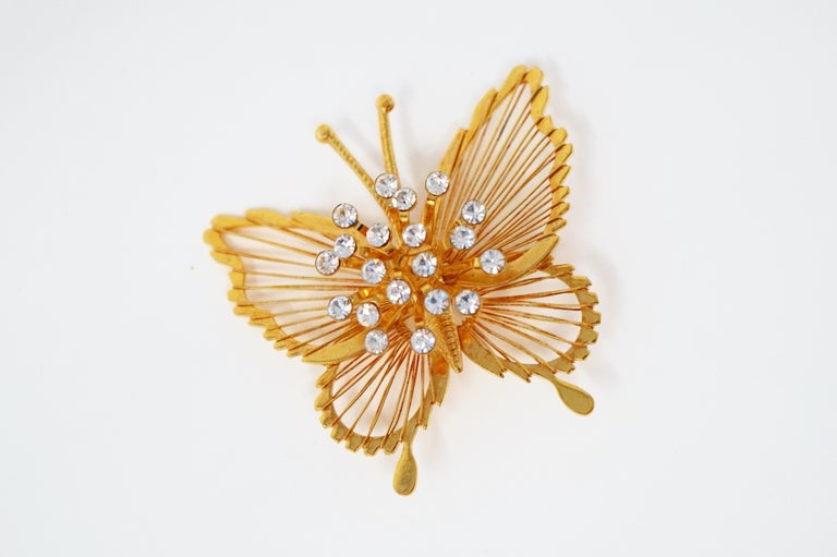 This gorgeous gilt butterfly brooch by Monet, circa 1970s, is a wonderful example of the quality and innovative designs that the coveted vintage costume jewelry brand is known for. With a shiny gold-plated finish and crystal rhinestone spray detail,
