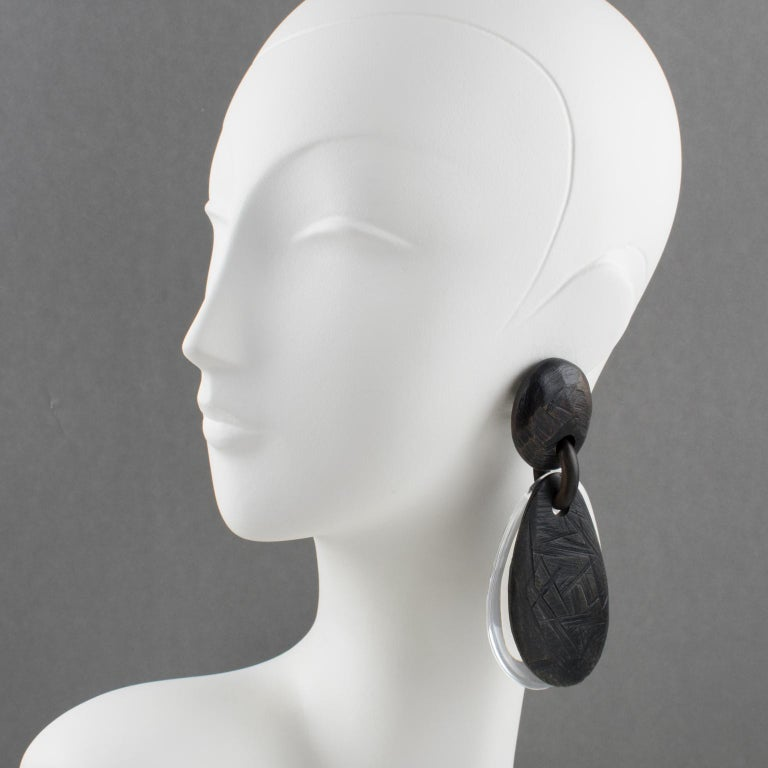 Spectacular oversized clip-on earrings by Gerda Lyngaard for Monies. Dangling pebble double teardrops shape built with transparent Acrylic or Lucite and Ebony wood with tribal carved texture. Marked