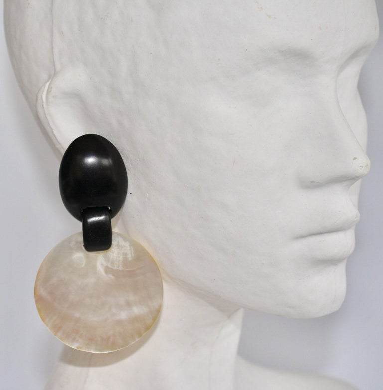 Shimmering mother of pearl drop disc clip earrings with ebony wood clip from Monies Denmark.