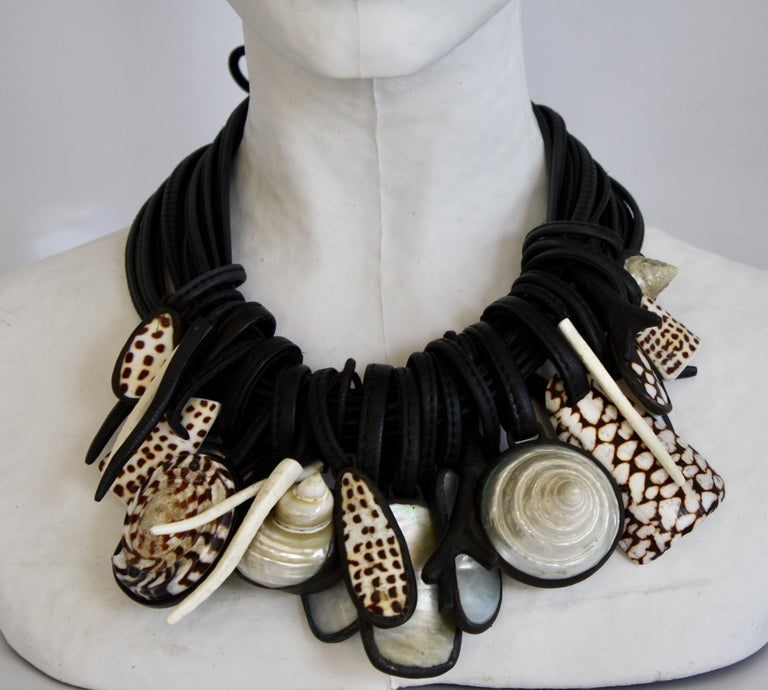 Shell, mother of pearl, rock crystal, and ebony multi pendant necklace on 11 strands of leather from Monies Denmark.