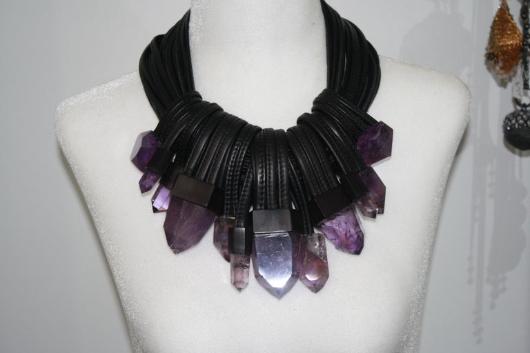22 strands of stitched leather with  a toggle clasp lock in ebony. 12 pendants made of  octogonal shaped amethysts . This is an amazing one of a kind!