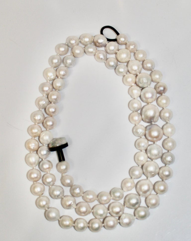 Pearl are threaded and knotted in gradual size. Clasp is made with horn and leather. Necklace can be wrapped around 3 times .