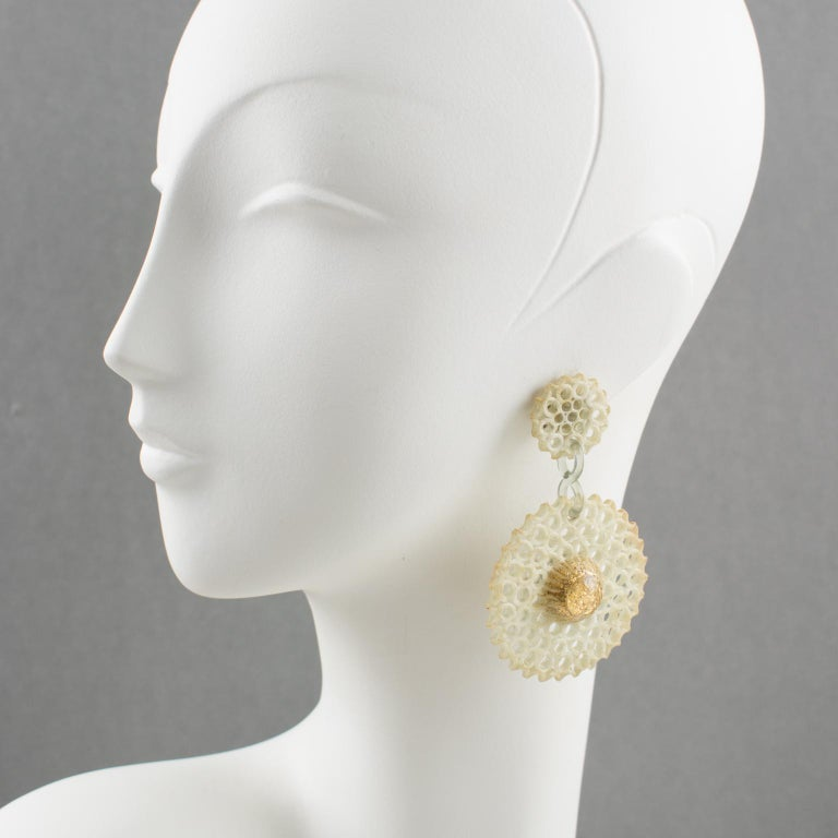 Refined Monique Vedie Talosel or resin clip-on earrings. Featuring floral dangling shape with a large disk with a textured pattern and see-thru carving like a sort of lace in an off-white color, topped with dimensional transparent resin cabochon