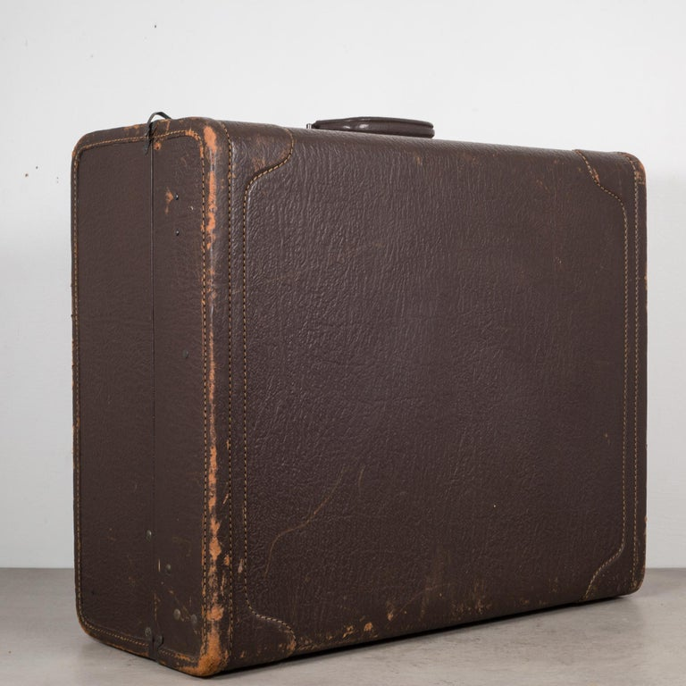 About  An all leather suitcase with stitched corners and a leather handle cover. The luggage is monogrammed