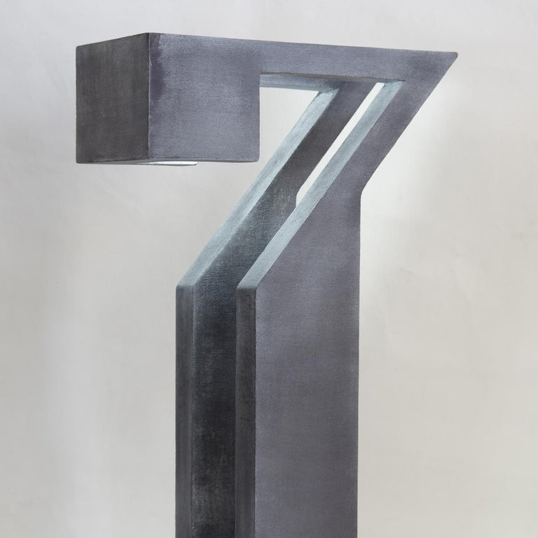 This imposing light-sculpture appears to be fashioned out of a single block of stone, its eclectic shape marked by rigorous linearity that reveals a captivating and unconventional profile. Handcrafted entirely of wood with a dark finish, the tall,