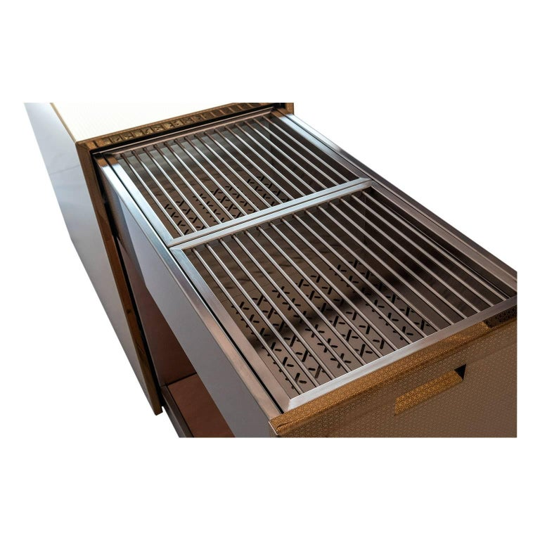 This monolithic charcoal barbecue is elegant and functional with sliding grills and accessories. The shell protects grills and accessories, it hides and then reveals the extractable soul in stainless steel, that becomes a comfortable surface for