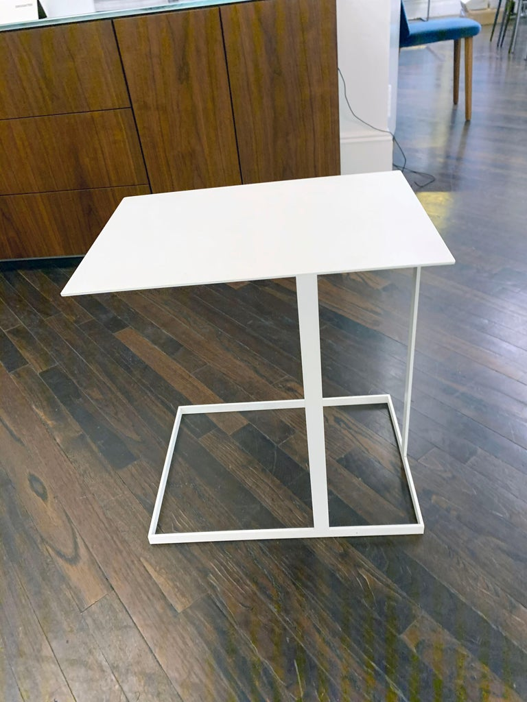 Annex is a multifunctional side table. The support has asymmetrical structures of flat metal strips. The functions of the free tabletop with projection are obvious and are ideal for working from the couch or lounge chair with a laptop, for putting