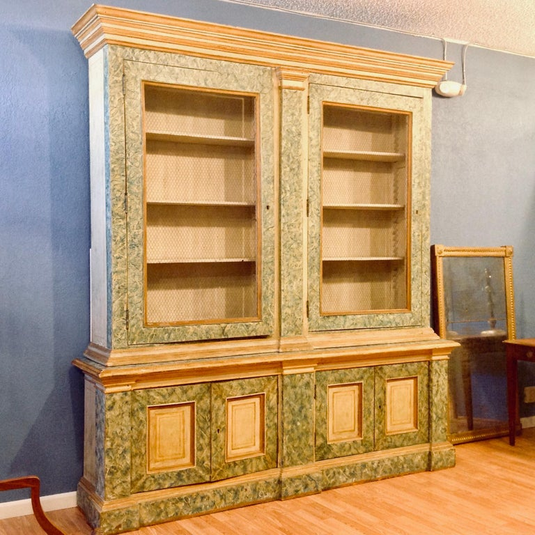 This fine piece is fashioned with faux marble finish. The upper doors are appointed with wire fronts; and the step back top is remarkably narrow in depth - enhancing its overall elegance.