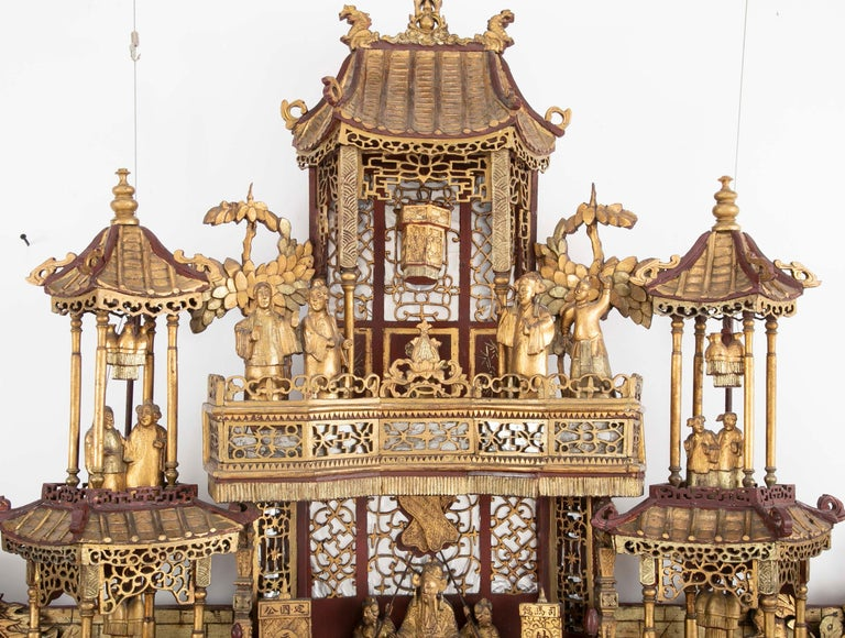 An exquisitely carved monumental 19th century altar piece with three dimensional carving including moving parts.