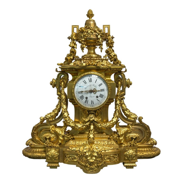 A fine quality monumental gilt bronze three-piece clock garniture. Comprising a fine quality large gilt bronze eight-arm figural rococo candelabra and a mantel clock, the black and white enameled dial inscribed Domange Rollin Paris.   Origin: