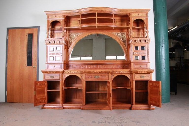 A rare and outstanding 19th century Victorian hand carved bar back procured from a pub in Massachusetts. The sideboard features solid cherrywood construction with stunning carved wood details, including carved faces, a floral motif and recessed