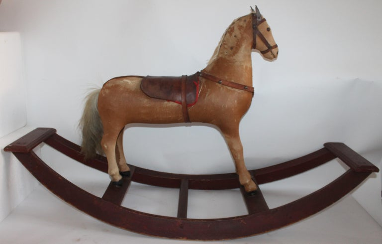 This very fine country rocking horse is not only fantastic looking and all original paint it is sturdy and strong. The pony skin is worn as well as the saddle but all in tack.