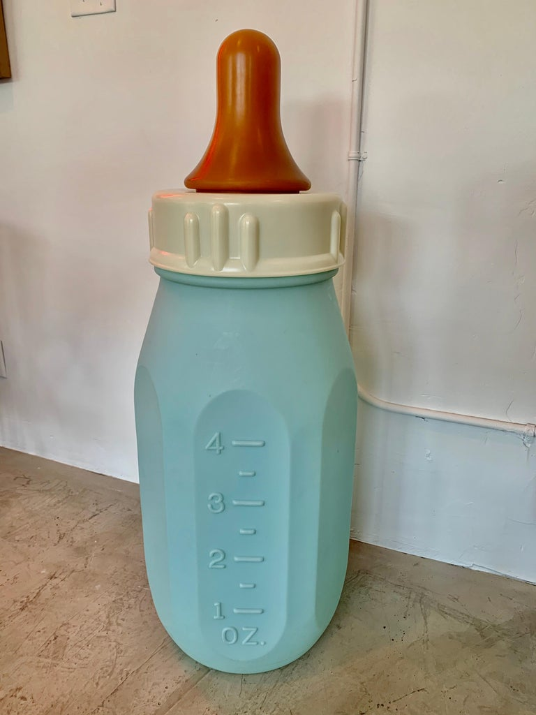 Gigantic baby bottle made in the 1970s. Hard plastic bottle with removable top and rubber nipple. Blue bottle with ounces on one side and milliliters on the other. At three and a half feet tall and 15