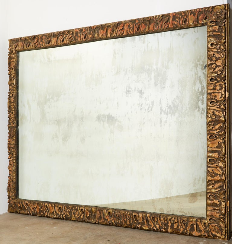 Monumental custom made mirror featuring a thick, hand-carved parcel gilt frame. The mirror is decorated with stylized acanthus leaves having an aged and distressed patina. The large glass has intentional wear and age also. Bespoke mirror made for a