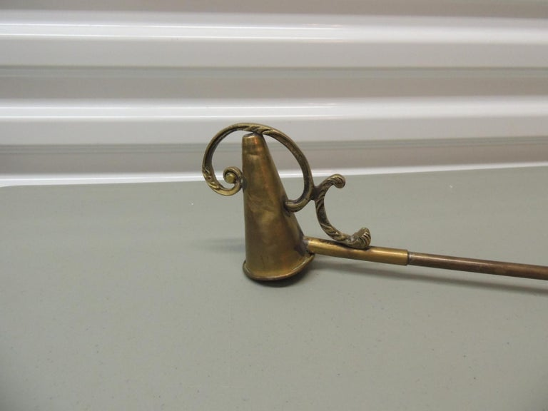 Monumental brass candle snuffer. Victorian details in brass and double grip handles. Cone shape snuffer. Ideal for candle chandeliers or to rest on a fireplace mantel. Size: 32