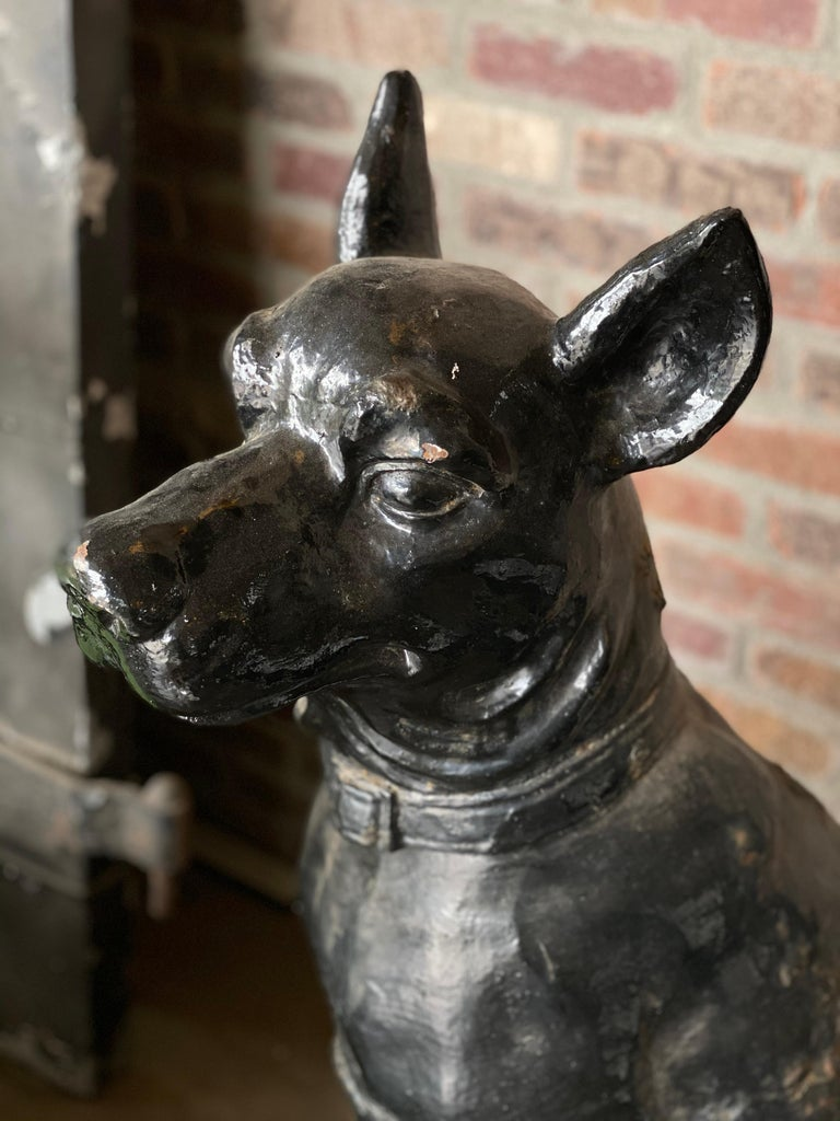 Monumentally scaled 19th century cast iron garden sculptures featuring a pair of dignified dogs with extraordinary presence. Original black painted finish is in good condition, with authentic age. Heads and tails are on opposite sides, with the