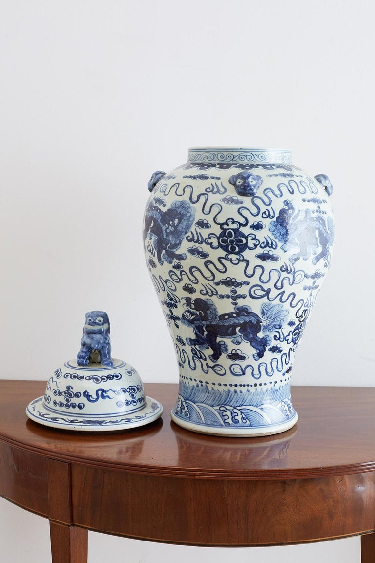 Monumental Chinese blue and white porcelain ginger jar or temple jar. Features hand-painted foo dogs or lions amid the clouds and fire with whimsical designs around them. The beautifully tapered form has mythical beast heads decorating the