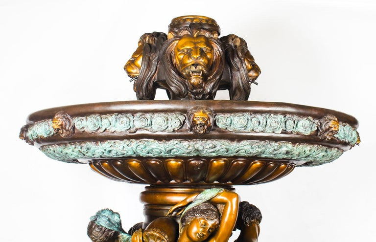 This is a monumental two-tier fountain sculpted in bronze in the neo-classical style, dating from the late 20th century.   This formidable fountain sprays water out of the top and out of four large roaring lion head cartouches. The water goes into