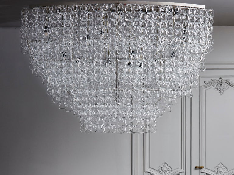Rare chandelier made of a steel structure and hundreds of handmade Murano glass hooks designed by Angelo Mangiarotti.  The oval shaped structure in polished steel easily blends behind all the glass pieces that are hung all around it. Between the