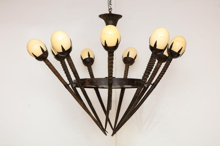 Very unusual chandelier, with gemsbok antler arms, topped with ostrich eggs. Center piece is cast bronze, and bottom is lined with animal skin.