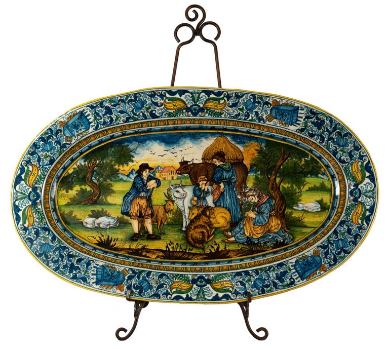 A monumental hand painted Italian Maiolica platter. Border with foliate design surrounding quivers of arrows, center reserve with a figural scene of peasants with their livestock resting under a tree.