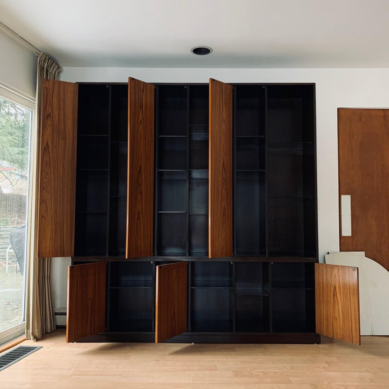 Impressive 1960s Harvey Probber wall unit/cabinet with 6 doors and wooden shelves. Exposed shelves are glass for displays. The cabinet is a dark stained mahogany and the doors are a light walnut. Plenty of storage and display options in a beautiful