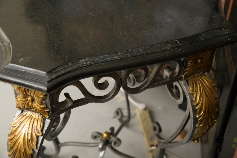 This is an impressive iron serpentine shaped console table with a scrolled design and decorated with gilt mounted acanthus leaf decoration. The table has an elaborate form of scrolls and curls which offers a sophisticate element for ones interior.